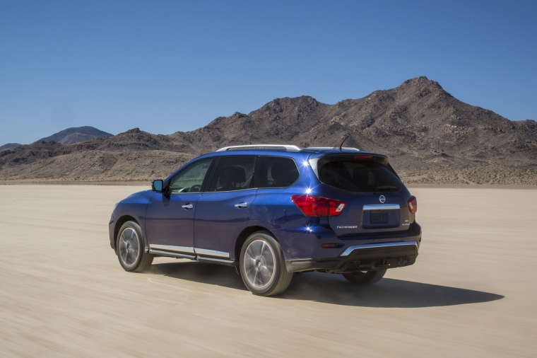 Picture of a driving 2020 Nissan Pathfinder Platinum 4WD in Caspian Blue Metallic from a rear left three-quarter perspective