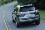 Picture of a driving 2014 Nissan Rogue SL AWD in Graphite Blue from a rear left perspective