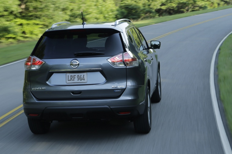 Picture of a driving 2016 Nissan Rogue SL AWD in Arctic Blue Metallic from a rear right perspective