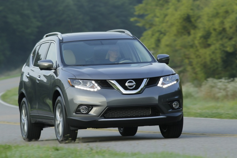 Picture of a driving 2016 Nissan Rogue SL AWD in Arctic Blue Metallic from a front right perspective
