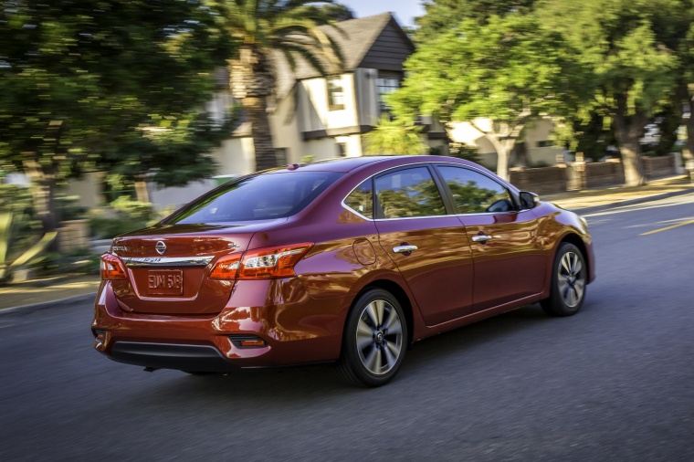 Driving 2017 Nissan Sentra SL in Cayenne Red Pearl Metallic from a rear right three-quarter view