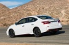 Driving 2017 Nissan Sentra NISMO in Aspen White from a rear left three-quarter view