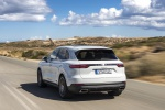 Picture of a driving 2019 Porsche Cayenne AWD in White from a rear left perspective