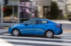 Driving 2016 Scion iA Sedan in Sapphire from a rear left three-quarter view