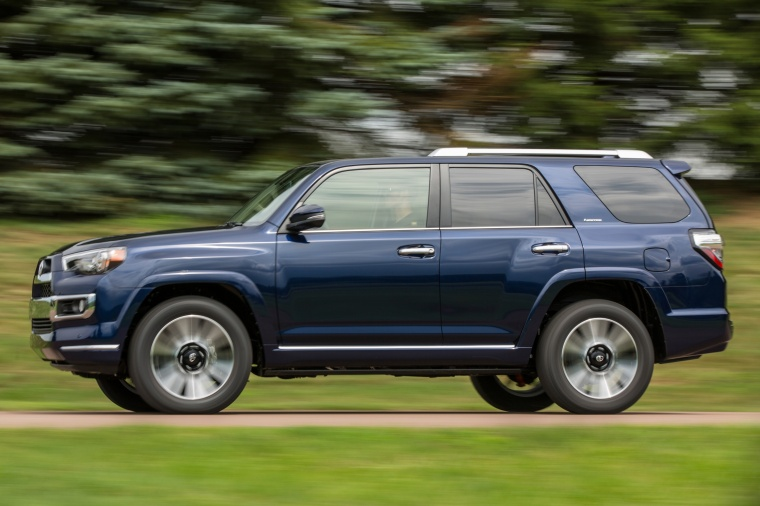 Picture of a driving 2016 Toyota 4Runner Limited in Nautical Blue Pearl from a side perspective