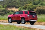 Picture of a driving 2016 Toyota 4Runner Trail in Barcelona Red Metallic from a rear left three-quarter perspective
