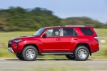 Picture of a driving 2019 Toyota 4Runner TRD Off Road in Barcelona Red Metallic from a side perspective