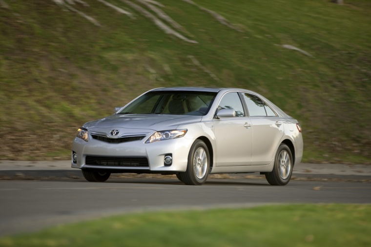 Driving 2010 Toyota Camry Hybrid in Classic Silver Metallic from a front left view
