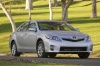 Driving 2010 Toyota Camry Hybrid in Classic Silver Metallic from a front three-quarter view