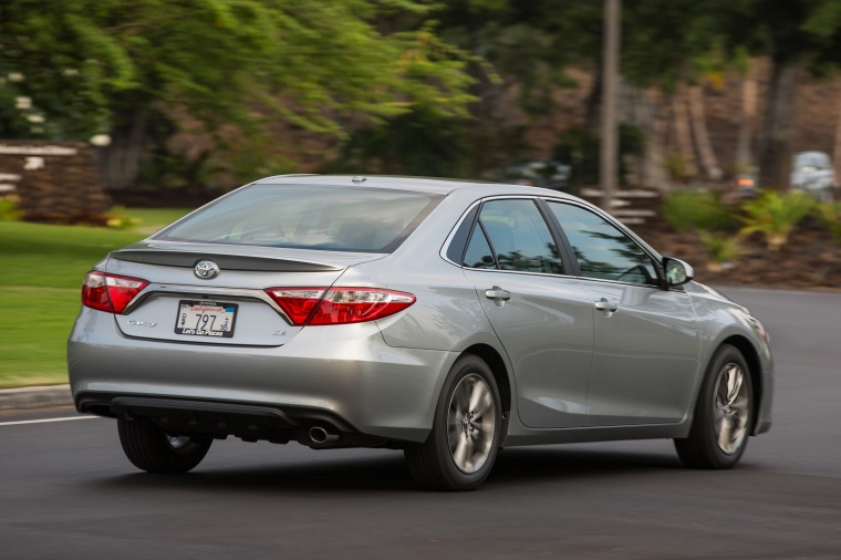 Driving 2015 Toyota Camry SE in Celestial Silver Metallic from a rear right three-quarter view