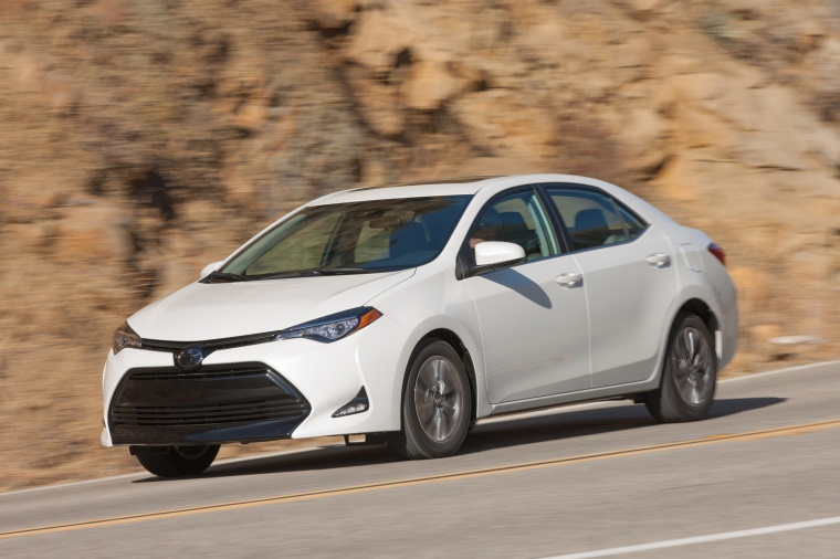 Driving 2017 Toyota Corolla LE Eco in Blizzard Pearl from a front left three-quarter view