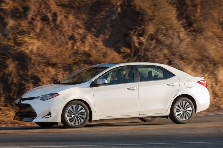 Driving 2017 Toyota Corolla LE Eco in Blizzard Pearl from a left side view