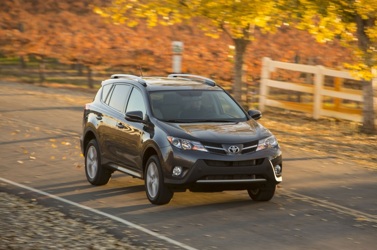 Picture of a driving 2014 Toyota RAV4 Limited in Magnetic Gray Pearl from a front right perspective