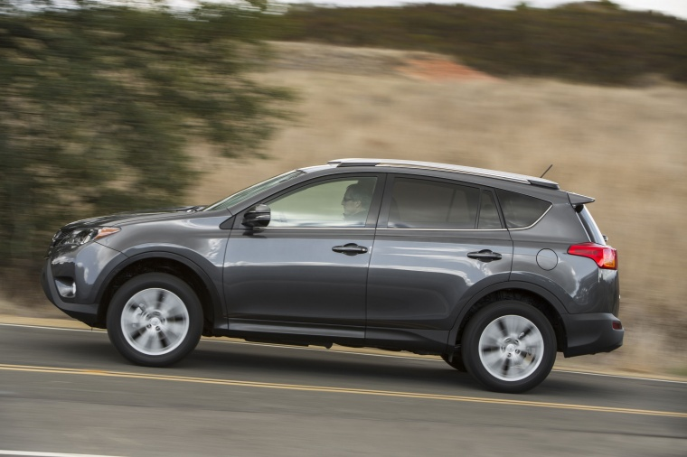 Picture of a driving 2014 Toyota RAV4 Limited in Magnetic Gray Pearl from a side perspective
