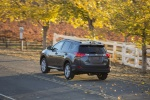 Picture of a driving 2014 Toyota RAV4 Limited in Magnetic Gray Pearl from a rear left three-quarter perspective