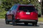 Picture of a driving 2016 Toyota RAV4 SE AWD in Barcelona Red from a rear left perspective