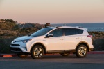 Picture of a driving 2016 Toyota RAV4 Hybrid XLE AWD in Super White from a front left three-quarter perspective