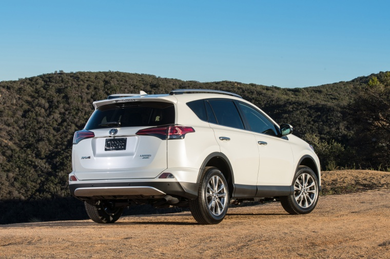 Driving 2017 Toyota RAV4 Limited AWD in Super White from a rear right three-quarter view