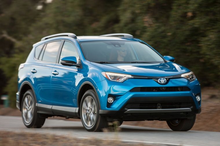 Picture of a driving 2017 Toyota RAV4 Hybrid Limited AWD in Electric Storm Blue from a front right three-quarter perspective