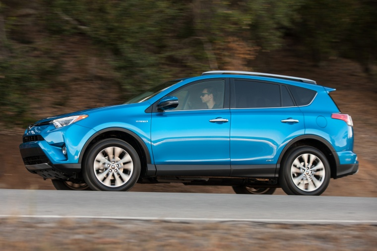 Driving 2017 Toyota RAV4 Hybrid Limited AWD in Electric Storm Blue from a side view