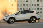 Picture of a driving 2017 Toyota RAV4 Hybrid XLE AWD in Super White from a side perspective