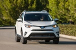 Picture of a driving 2017 Toyota RAV4 Hybrid XLE AWD in Super White from a front right perspective