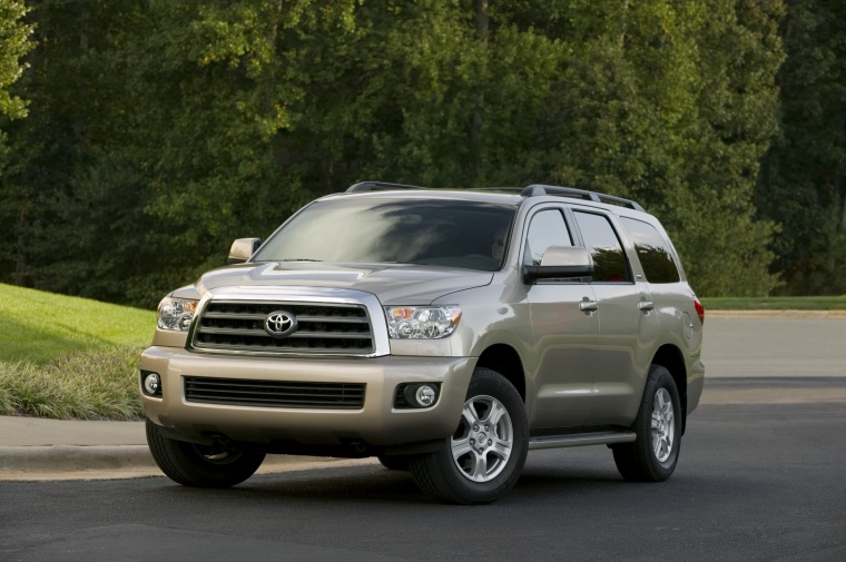 Picture of a driving 2016 Toyota Sequoia in Sandy Beach Metallic from a front left three-quarter perspective