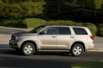 Picture of a driving 2016 Toyota Sequoia in Sandy Beach Metallic from a left side perspective