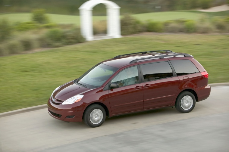 Driving 2010 Toyota Sienna LE in Salsa Red Pearl from a left side top view