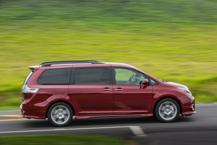 Driving 2017 Toyota Sienna SE in Salsa Red Pearl from a side view