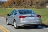 Driving 2018 Volkswagen Passat Sedan in Reflex Silver Metallic from a rear view