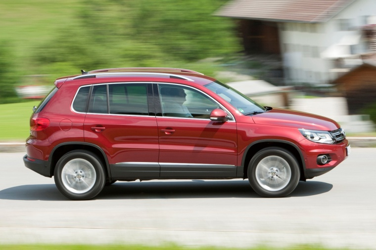 Driving 2012 Volkswagen Tiguan in Wild Cherry Metallic from a right side view