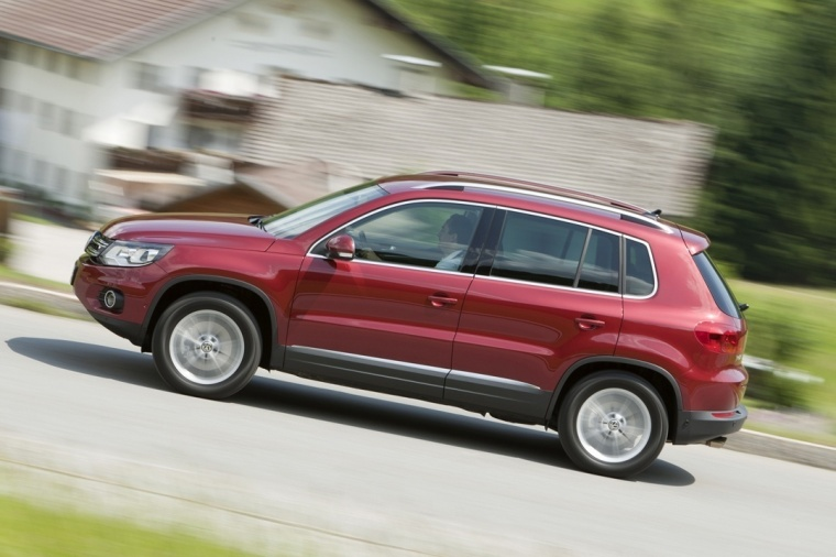 Driving 2016 Volkswagen Tiguan in Wild Cherry Metallic from a left side view