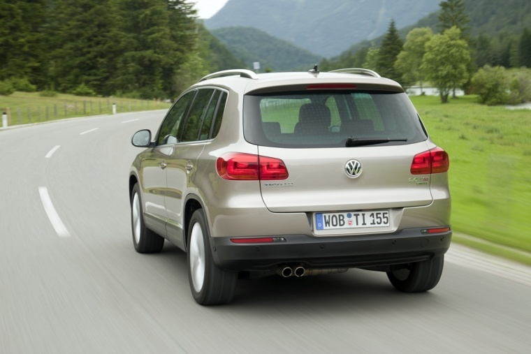 Driving 2016 Volkswagen Tiguan in White Gold Metallic from a rear view