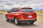 Picture of a driving 2019 Volkswagen Tiguan SEL in Habanero Orange Metallic from a rear left three-quarter perspective