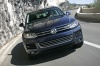 Driving 2014 Volkswagen Touareg Hybrid in Night Blue Metallic from a frontal view