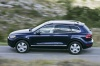 Driving 2014 Volkswagen Touareg Hybrid in Night Blue Metallic from a side view