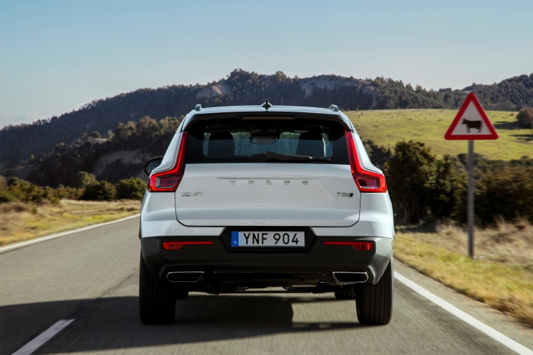 Driving 2020 Volvo XC40 T5 R-Design AWD in Crystal White Metallic from a rear view