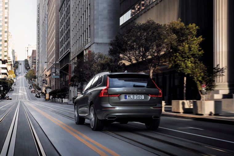 Picture of a driving 2019 Volvo XC60 T6 AWD in Pine Gray Metallic from a rear left perspective
