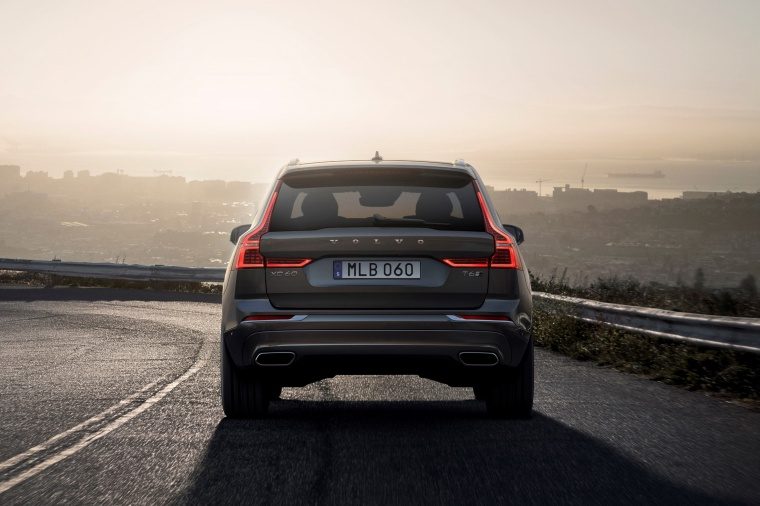 Picture of a driving 2019 Volvo XC60 T6 AWD in Pine Gray Metallic from a rear perspective