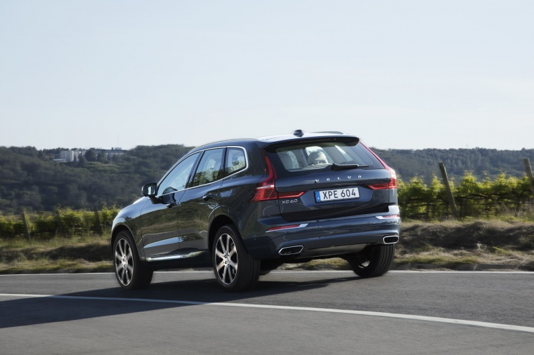 Picture of a driving 2019 Volvo XC60 T6 AWD in Denim Blue Metallic from a rear left three-quarter perspective