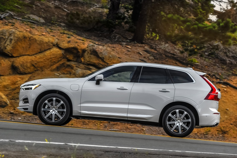 Picture of a driving 2019 Volvo XC60 T8 eAWD in Crystal White Pearl Metallic from a side perspective