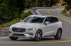 Picture of a driving 2019 Volvo XC60 T8 eAWD in Crystal White Pearl Metallic from a front left three-quarter perspective