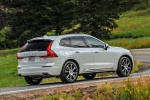 Picture of a driving 2019 Volvo XC60 T8 eAWD in Crystal White Pearl Metallic from a rear right three-quarter perspective
